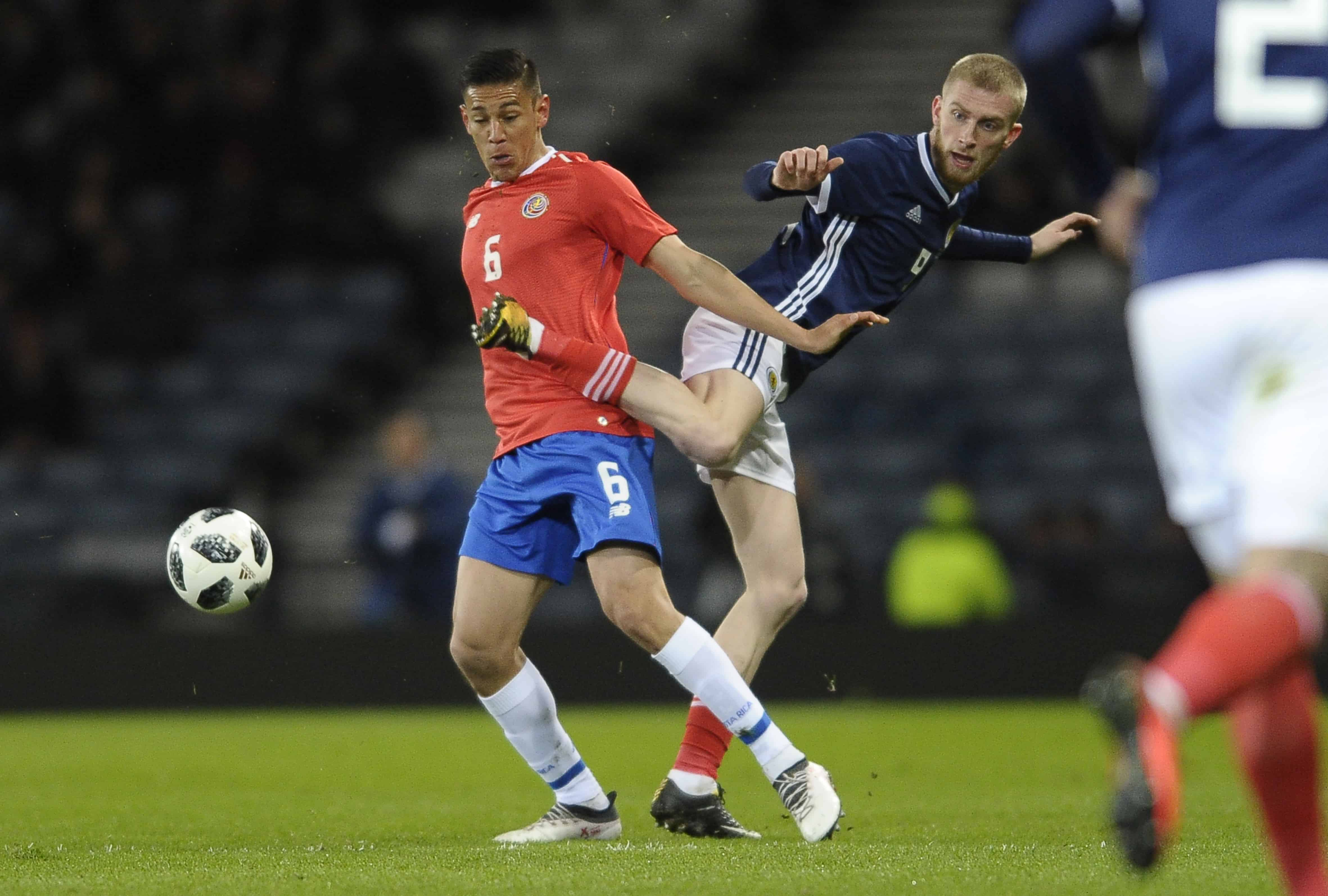 Costa Rican defender Oscar Duarte (L) vies with Scottish striker Oliver McBurnie during the international friendly between Scotland and Costa Rica at Hampden Park in Glasgow, Scotland on March 23, 2018.