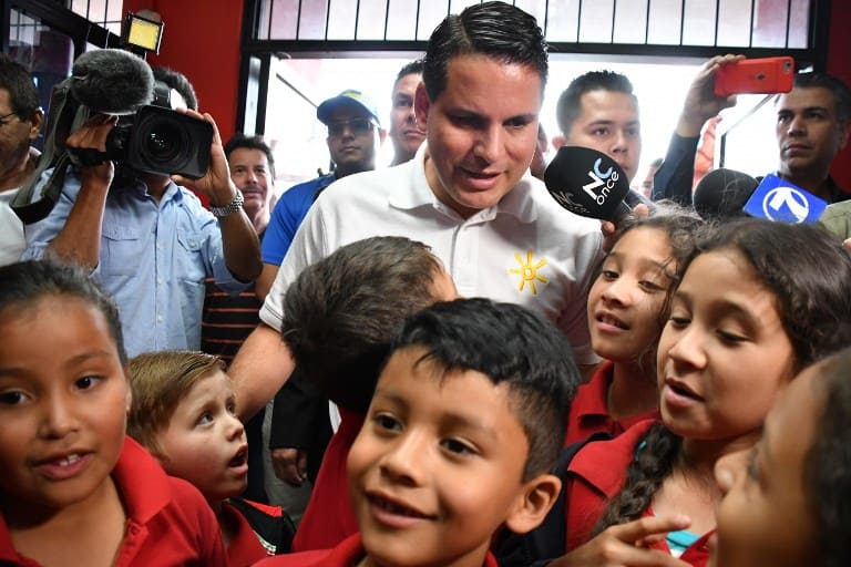 Costa Rican presidential candidate, Fabricio Alvarado, of the National Restoration Party (PRN), is surrounded by children during his visit to the headquarters of the nonprofit organization Works of the Holy Spirit, in San Jose on March 31, 2018, on the eve of country's runoff election.