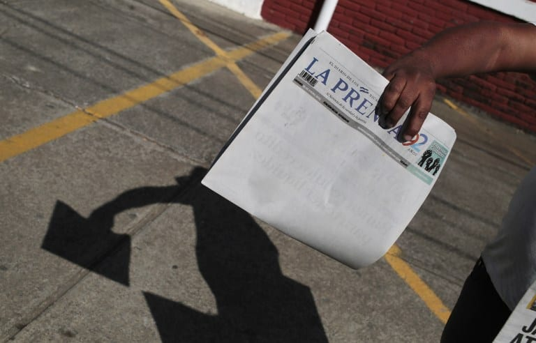 "A vendor selling newspapers shows the edition of ""La Prensa"""