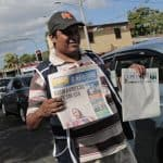 """A vendor selling newspapers holds an edition of """"La Prensa"""""""