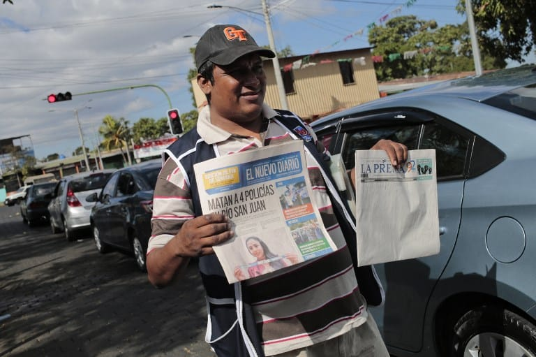 "A vendor selling newspapers holds an edition of ""La Prensa"""