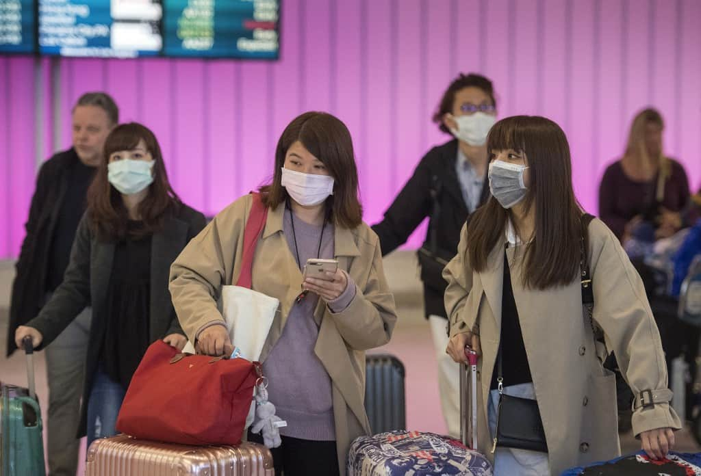 Passengers wear protective masks to protect against the spread of the Coronavirus