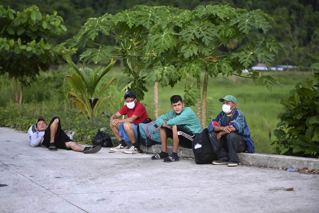 Honduran migrants, part of a US-bound caravan, rest after being intercepted by Guatemalan Army members in San Luis, Peten department, Guatemala on October 3, 2020.
