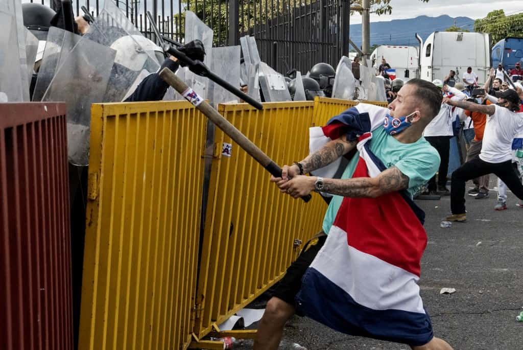 A protester wrapped in a Costa Rican flag and with a metal tube confronts riot police during a protest against the government's motion to increase taxes in order to reach a credit agreement with the International Monetary Fund (IMF), outside the presidential house in San Jose, on October 12, 2020.