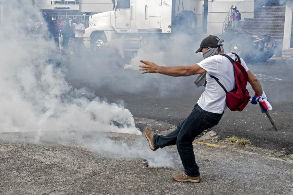 A protester kicks a tear gas canister back at riot police during a protest against the government's motion to increase taxes in order to reach a credit agreement with the International Monetary Fund (IMF), outside the presidential house in San Jose, on October 12, 2020.