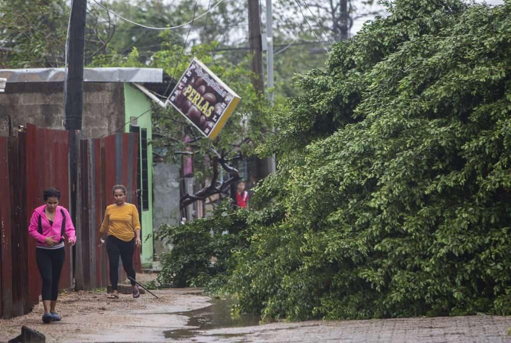 Women walk next to fallen trees as Hurricane Eta makes landfall in Bilwi, Puerto Cabezas, Nicaragua, on November 3, 2020.