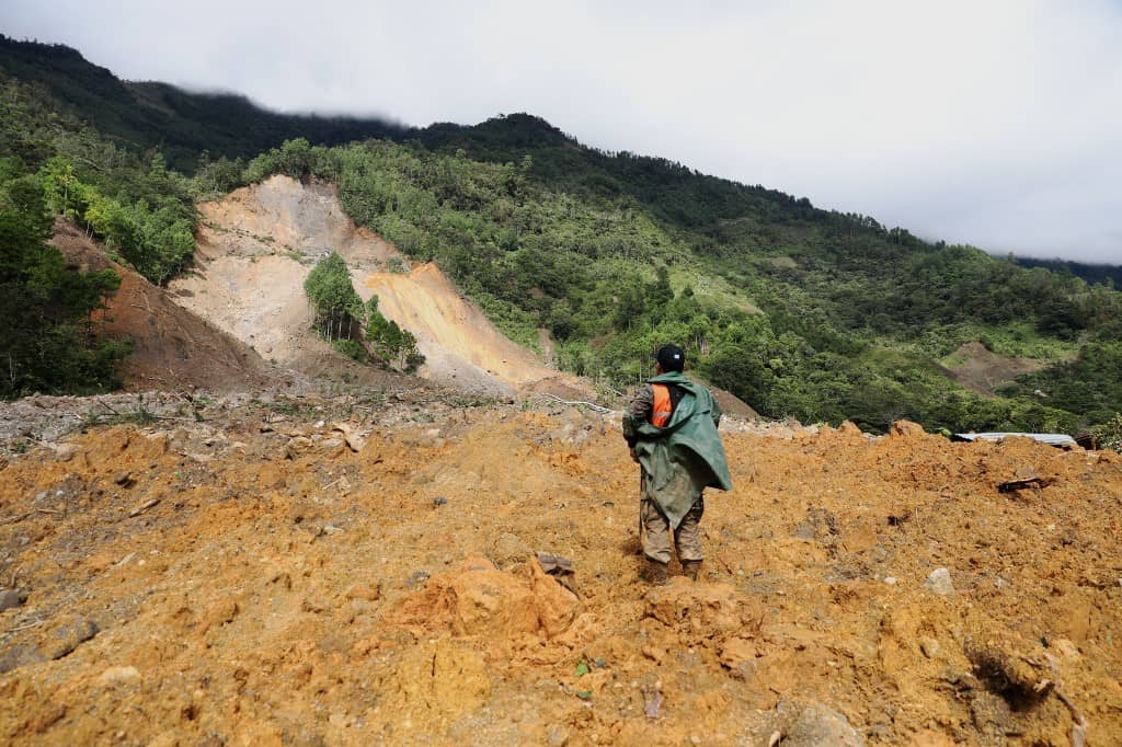 A rescue worker searches for victims of a mudslide where it is estimated that dozens of people died last Thursday, caused by the passage of Hurricane Eta, in the village of Queja, in San Cristobal Verapaz, Guatemala on November 7, 2020.