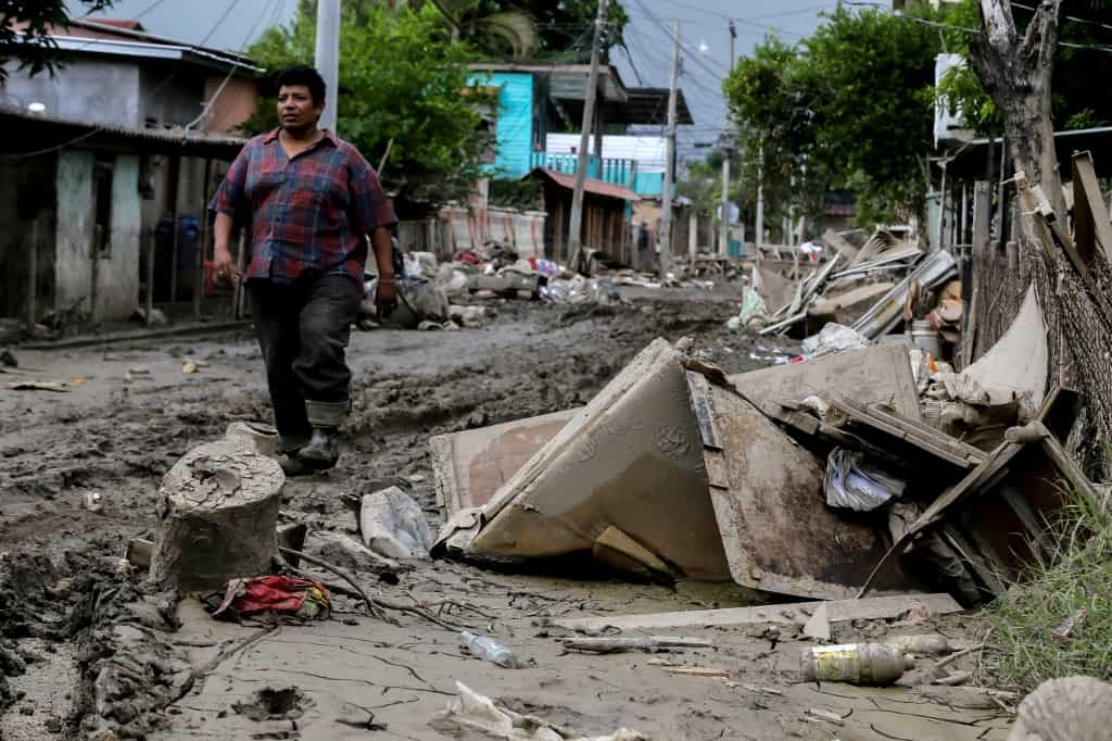 A man walks along a damaged street after the passage of Hurricane Eta in La Lima, Cortes, Honduras, on November 16, 2020 as Hurricane Iota -- upgraded to Category 5 -- moves over the Caribbean towards the Nicaragua-Honduras border.
