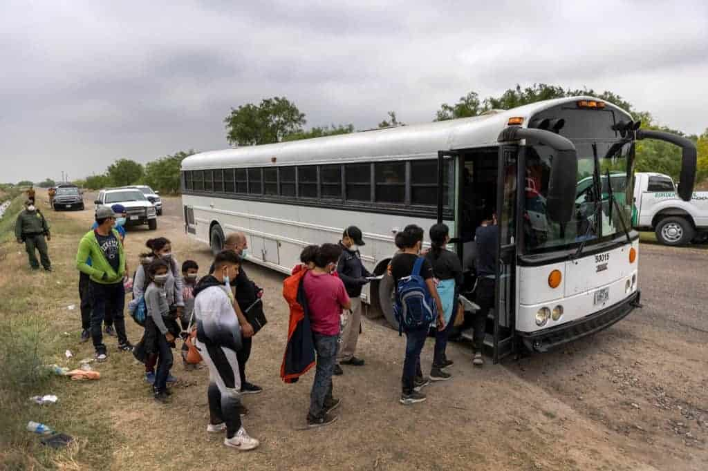 Central American families board a U.S. Customs and Border Protection bus for transport to an immigrant processing center after crossing the border from Mexico