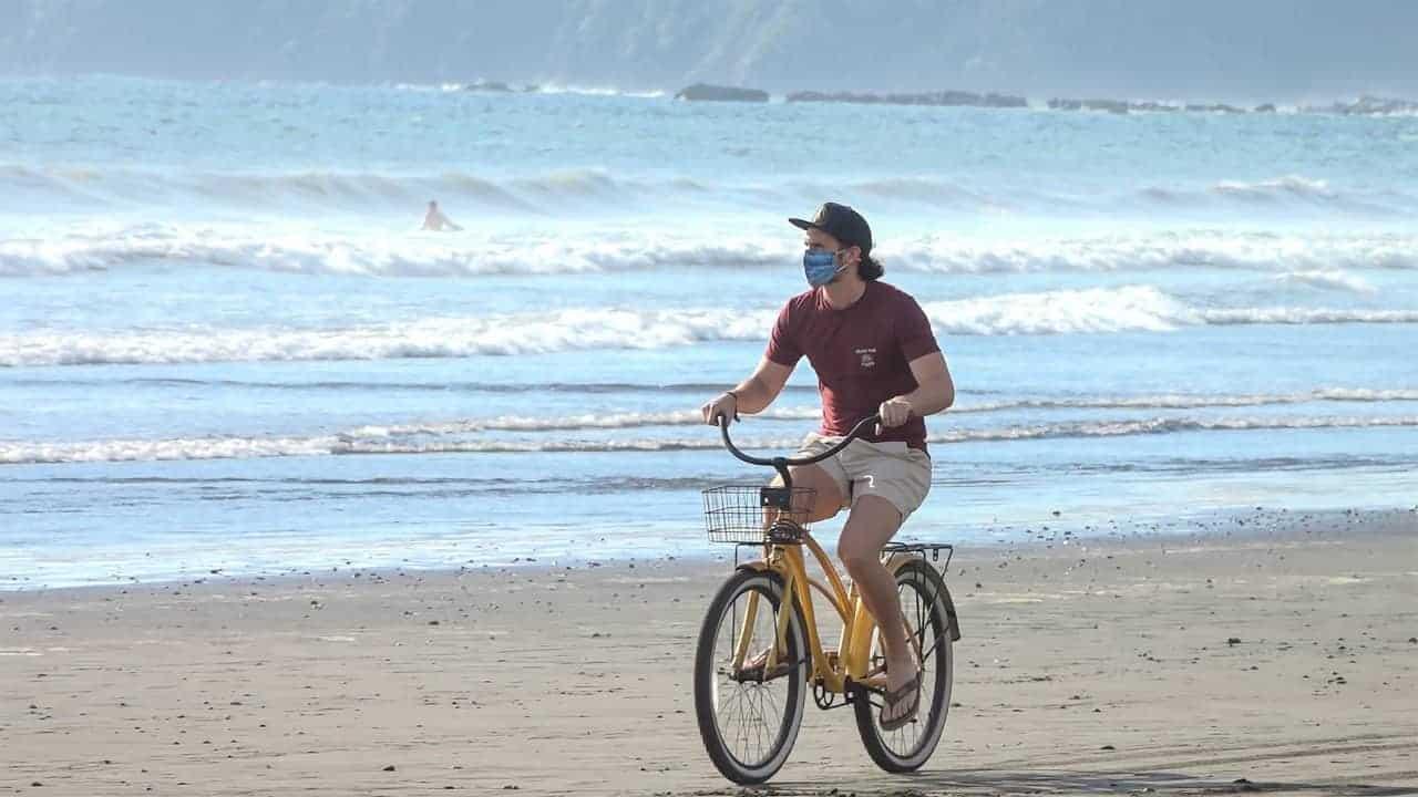 A tourist bikes on a Costa Rican beach.